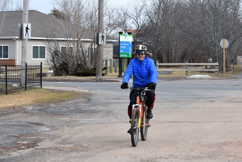 Frank Graham crossing busy Willow Street to continue on the Cobequid Trail.