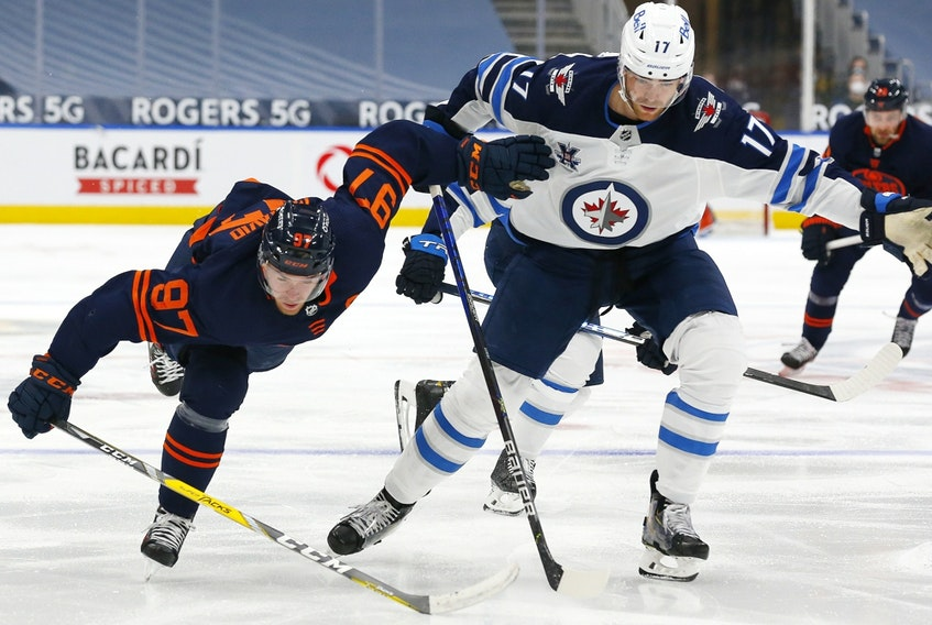 Winnipeg Jets forward Adam Lowry (17) trips up Edmonton Oilers forward Connor McDavid (97) at Rogers Place in Edmonton on Mar 20, 2021.