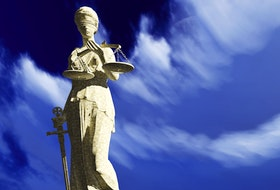A Lady Justice sculpture depicts a blindfolded woman with sword and scale