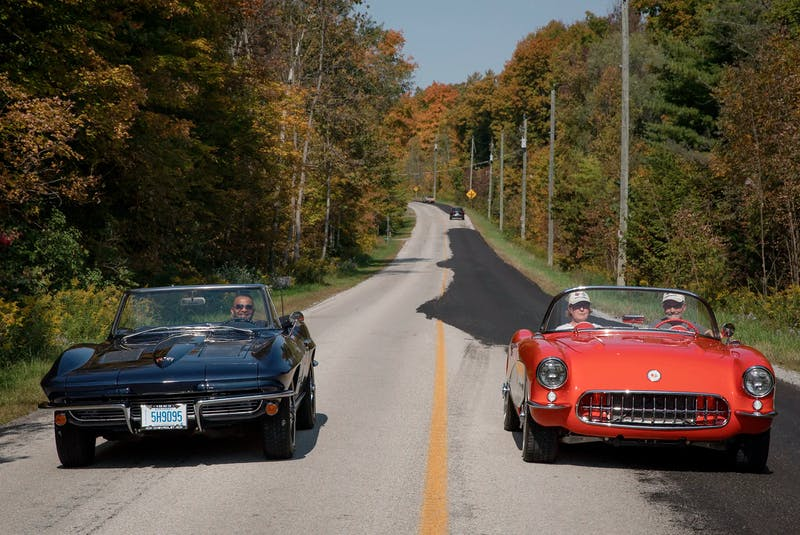 Rick Patel, left, drives his 1963 Chevrolet Corvette alongside a couple in a 1957 Corvette roadster. Clayton Seams/Postmedia News - POSTMEDIA