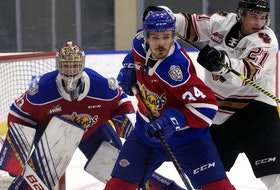Edmonton Oil Kings centre Kaid Oliver (34) battles the Calgary Hitmen's Riley Fiddler-Schultz (21) in front of goaltender Sebastian Cossa (33) in Edmonton on March 26, 2021.
