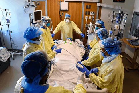 Healthcare workers get ready to prone a 47-year-old woman who has COVID-19 and is intubated on a ventilator in the intensive care unit at Toronto's Humber River Hospital on Tuesday, April 13, 2021.