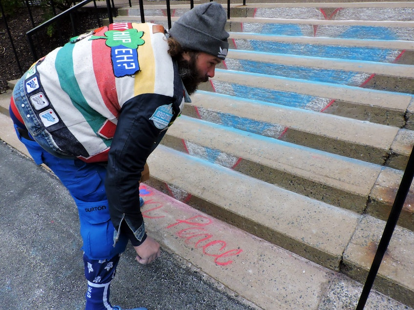 Halifax artist and musician Darcy Howat decorates the steps of Halifax's Cathedral of All Saints with chalk hearts prior to Saturday's provincial memorial service for Prince Philip, the Duke of Edinburgh. - Stephen Cooke