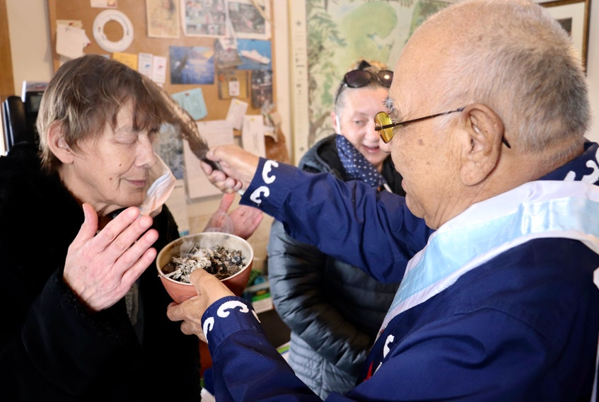 Janet McLeod, left, receives the cleansing smoke of the Mi'kmaq smudging ceremony from Keptin John Joe Sark.