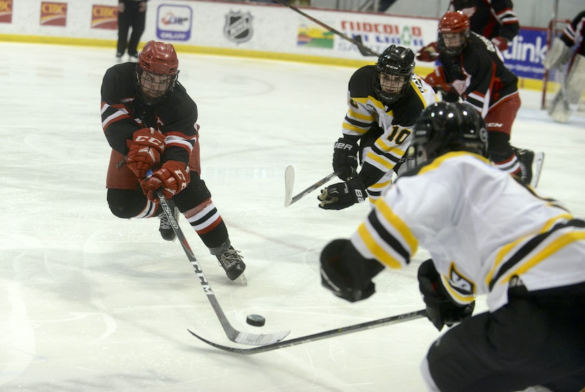 Arsenault's Fish Mart Western Red Wings left-winger Alex Morrissey, left, tries to chip the puck past A&S Scrap Metal Metros defenceman Jason Poley during Game 3 of the Island Junior Hockey League final.