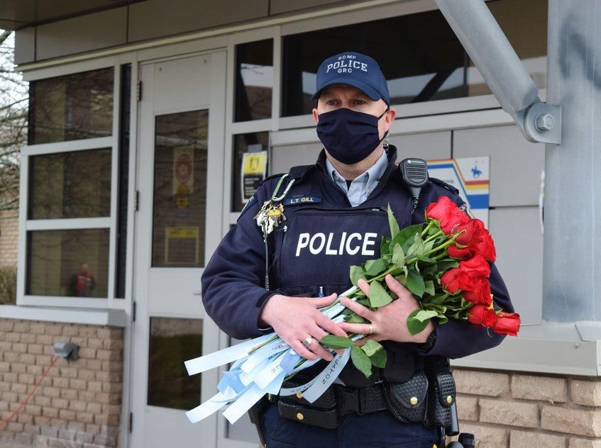 Family members each gave roses with the victims' names to an RCMP officer. - Chelsey Gould