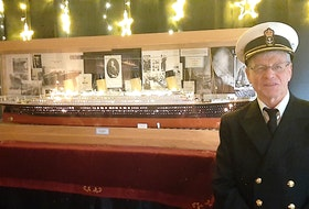 Dressed in a ship captain's uniform, Ray Johnson poses in front of the scale model of the Titanic that took him a dozen years to build. — Facebook/Pauline Yetman