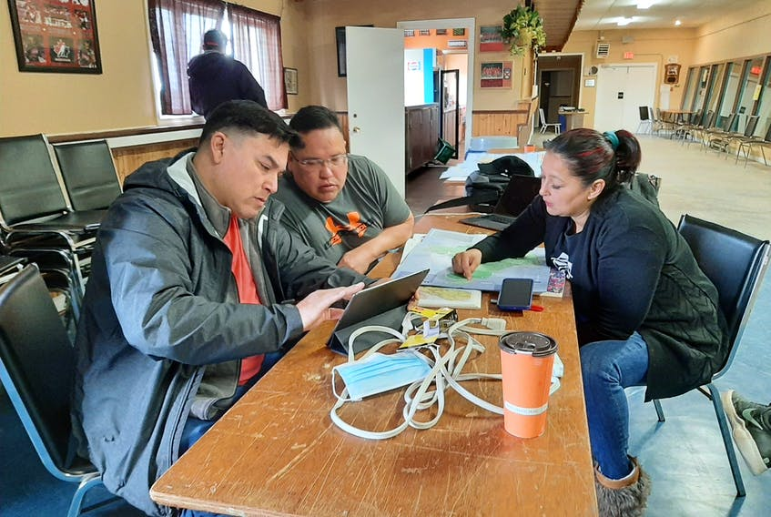 Josh Augustine and Richard Levi from Elsipogtog First Nation and Starr Paul from Eskasoni First Nation look at maps of the Cape Breton coastline as part of the search for Jumbo Sock. ARDELLE REYNOLDS/CAPE BRETON POST