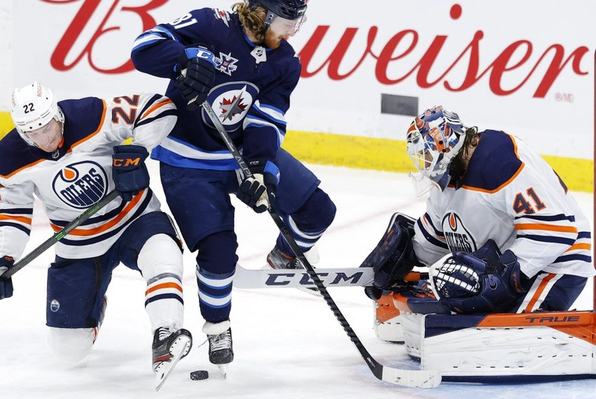 Edmonton Oilers defenseman Tyson Barrie (22) and Winnipeg Jets left wing Kyle Connor (81) jump from the puck in front of Edmonton Oilers goaltender Mike Smith (41) in the second period at Bell MTS Place on April 17, 2021.