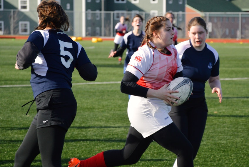 Katie Clemens of the Riverview Ravens, middle, blows through a pair of Sydney Academy Wildcats players during Cape Breton High School Rugby League girls play at the Cape Breton Health Recreation Complex in Sydney on Monday. Clemens had two tries in the game. Riverview won the contest 86-0.