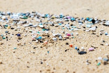 Microplastics washed up on the shore of the ocean. STOCK