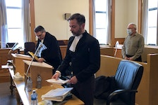 Former Anglican priest Robin Barrett stands in the dock in Courtroom 2 at Newfoundland and Labrador Supreme Court in St. John's Monday, behind his lawyer, Mark Gruchy (left) and prosecutor Shawn Patten.