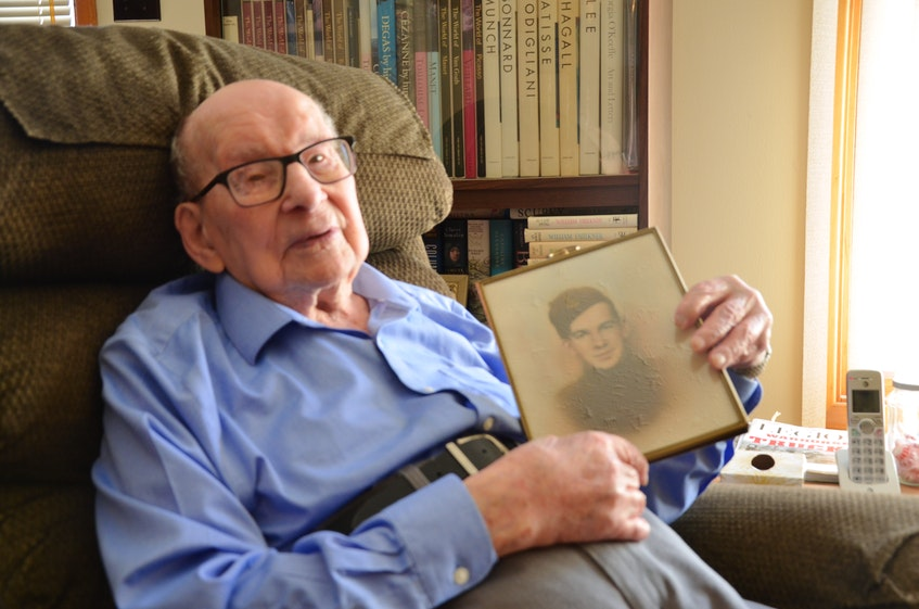104-year-old Hormidas Fredette of New Minas with a photo of himself as a young soldier in the Second World War. Fredette survived some three years and eight months being held as a prisoner of war by the Japanese. KIRK STARRATT