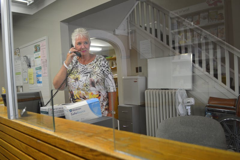 Dorothy Ferguson, operator with the walk-in clinic located in the Sydney Family Practice Centre on Kings Road in Sydney, behind a protective glass barrier at the reception desk in this Cape Breton Post file photo. Sharon Montgomery-Dupe/Cape Breton Post