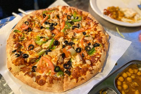 The Butter Chicken Pizza comes with olives, tomatoes and green peppers.