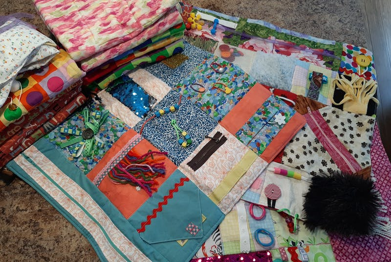 Fidget quilts are often created with things like buttons, zippers, ribbons and different fabrics. They help to keep dementia patients' hands busy and their minds calm. - Contributed