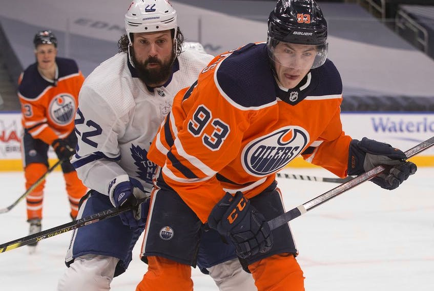The Edmonton Oilers' Ryan Nugent-Hopkins (93) battles the Toronto Maple Leafs' Zach Bogosian (22) during first period NHL action at Rogers Place, in Edmonton Saturday Feb. 27, 2021. Photo by David Bloom