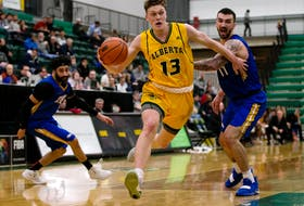The University of Alberta Golden Bears' Adam Paige (13) breaks past the University of British Columbia Thunderbirds' Manroop Clair (3) and Patrick Simon (11) during Game 3 of their Canada West playoff series in Edmonton on Feb. 24, 2019.
