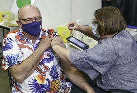 Retired nurse Roberta Banfield gives Dr. Robert Strang, Nova Scotia's chief medical officer of health, his first dose of COVID-19 vaccine Tuesday, April 20, 2021, at the Halifax Forum immunization clinic in Halifax.