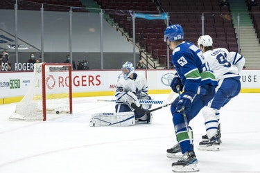 Canucks forward Bo Horvat (53) scores the winning goal in overtime against Toronto Maple Leafs goalie Jack Campbell, who has now lost three in a row after winning 11 straight, in Vancouver on Sunday night.
