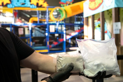 A police officer handles two bags of drugs at the Karebear Playland facility in Brampton.