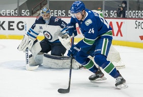 Winnipeg Jets' Connor Hellebuyck defends the goal against Vancouver Canucks forward Jimmy Vesey at Rogers Arena.