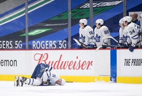 The Leafs' Zach Hyman lies on the ice after colliding with Canucks' Alexander Edler during their game in Vancouver on Sunday night. Darryl Dyck/THE CANADIAN PRESS
