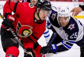 Ottawa Senators centre Josh Norris (9) wins a faceoff against Winnipeg Jets centre Paul Stastny.