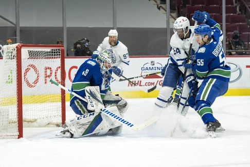 Vancouver Canucks defenceman Guillaume Brisebois, right, checks Toronto Maple Leafs forward Wayne Simmonds as Canucks goalie Braden Holtby makes a save in the first period of Sunday's NHL game at Rogers Arena in Vancouver. It was Vancouver's first game since March 24 due to COVID-19. Brisebois, 23, was the captain of the Charlottetown Islanders during the 2016-17 Quebec Major Junior Hockey League season. Sunday was his first game of the season with Vancouver.