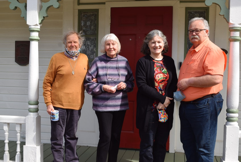 Paul and Jan Zann, left, Kathleen MacPherson and and Don Pugsley stand outside the John L. Doggett House, a provincial heritage property. They want town council to reconsider its planned consultation process for amendments that could allow a nearby heritage designated property to be rezoned for a 52-unit residential building.