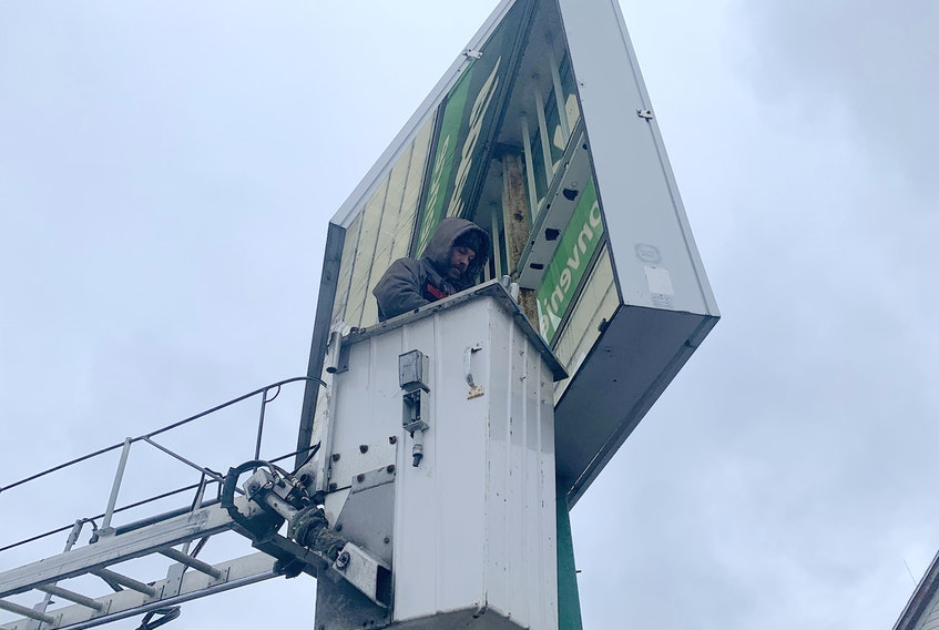 John Forget of Seven Signs Ltd. was in the bucket of a boom truck as he worked on the sign at Needs Convenience in Coxheath on Monday morning. Forget said the sign needed electrical repairs and upgrades. Chris Connors • Cape Breton Post