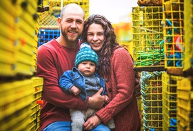 Millen Boyd and Fallon Conway with their son Loki amongst their lobster traps two weeks ago. Boyd and his crew were saved Wednesday off Whitehead when his boat capsized. Photo by Kennedy Fraser.