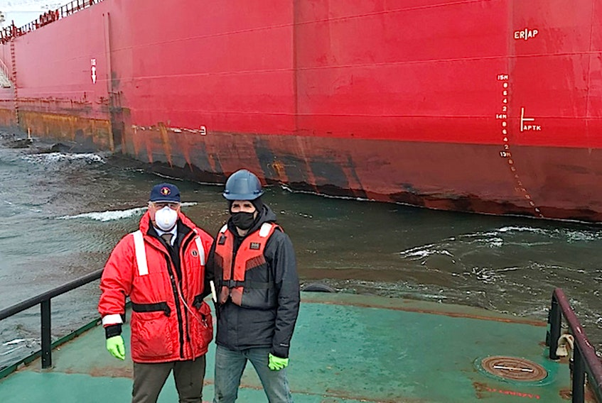 Iaian Langley, left, a harbour pilot with the Atlantic Pilotage Authority, and Greg Cogswell, a deckhand, on the harbour launch, a work boat that services the harbour, after delivering the care package to the STI San Telmo which is anchored off Port Hawkesbury, Tuesday. CONTRIBUTED