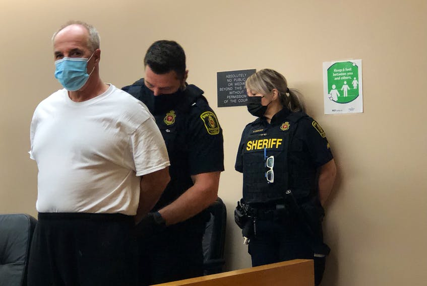 Sheriff's officers at provincial court in St. John's escort Dennis Peter Murphy, 60, into the courtroom for his sentencing hearing Wednesday.