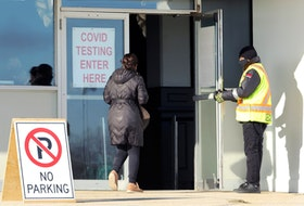 A security guard holds the door for a woman at the entrance to a COVID-19 testing site in Winnipeg.