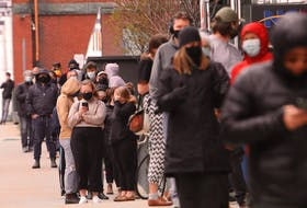 A lineup of people going on for rapid COVID-19 testing starts at the front door on Argyle Street and wraps around Sackville Street and Market Street in downtown Halifax Thursday.