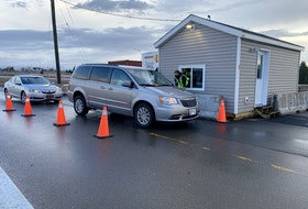 A conservation officer with the province's Environment and Climate Change Department checks on a vehicle coming into the province at Fort Lawrence on Thursday morning. New restrictions were put into place at 8 a.m. Thursday restricting entrance to Nova Scotia.