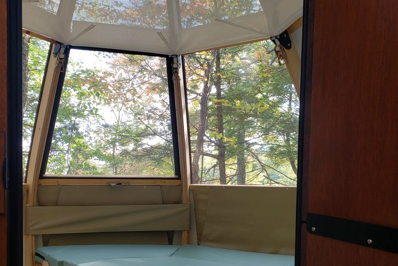 The interior of the Ôasis 'duplex' showing the convertible table/bed on the main level and suspended hammock loft above - Parks Canada