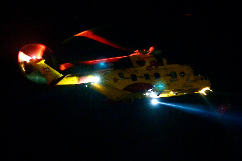 A cormorant helicopter flies over the search area in Flatrock Wednesday night. - Keith Gosse/The Telegram