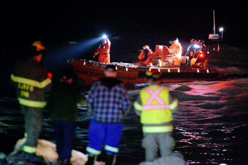 Rescue personnel search for a missing person who reportedly disappeared into the waters near the breakwater in Flatrock Wednesday night. - Keith Gosse/The Telegram