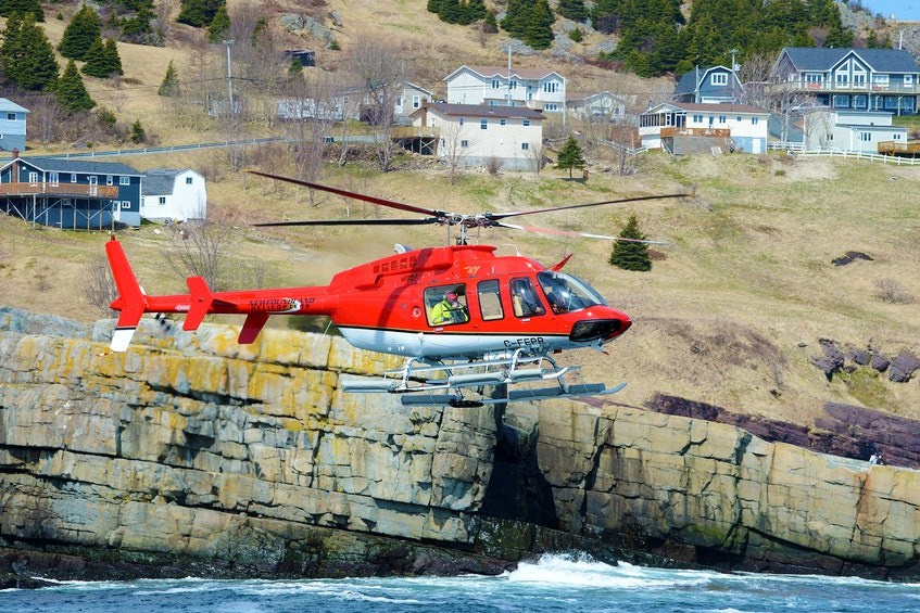 First responders were aided by a privately owned helicopter during the Thursday morning search for a man who went missing in the waters off Flatrock on Wednesday night. - Keith Gosse/The Telegram