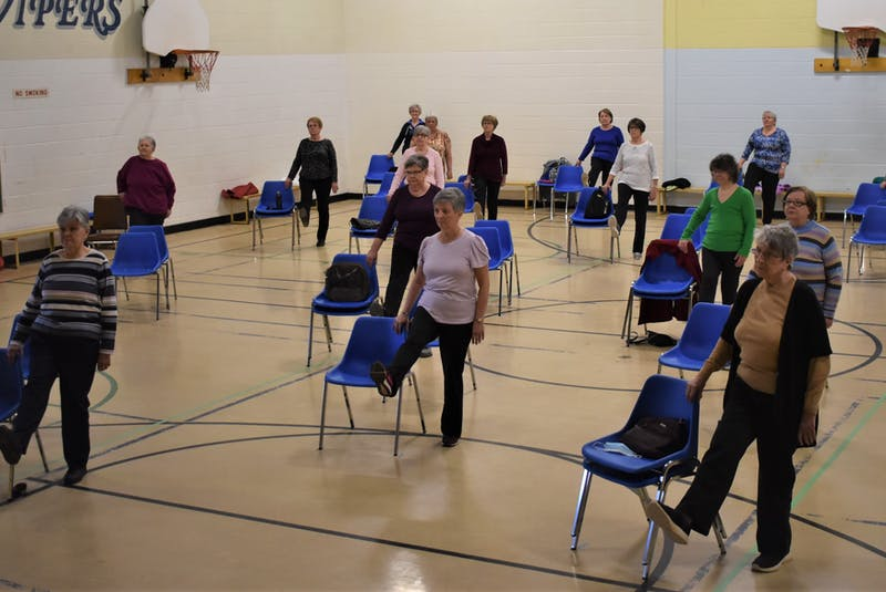 Participants in the Chair Exercise class at the Westville Municipal Building lift one leg while using theirs chairs for support.  - Richard MacKenzie