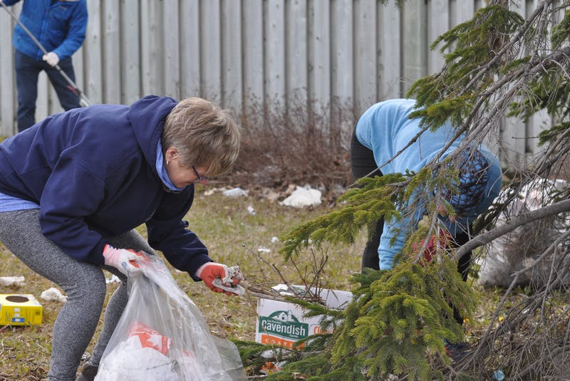 Dawn Taylor (left) and Doris Cormier pick up litter that collected in a green space on St. Mark's Avenue in Corner Brook on Thursday. - Diane Crocker
