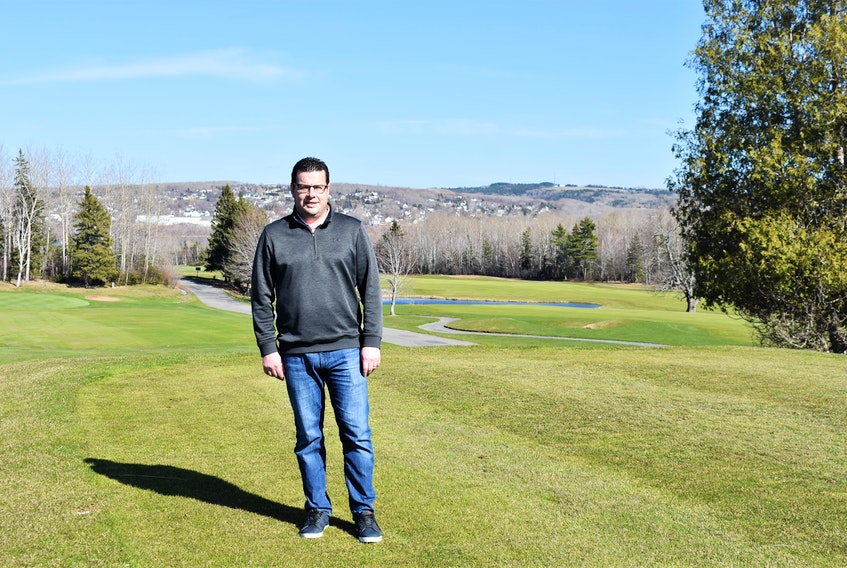 Abercrombie Golf and Country Club director of golf Jon Garron stands near the clubhouse, with views of lush fairways in the backdrop.