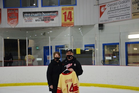 Darren and Glenda Hutchinson hold the jersey their son, Alex, wore with the Arsenault's Fish Mart Western Red Wings at the Evangeline Recreation Centre on Wednesday night. The Red Wings defeated the Sherwood-Parkdale A&S Scrap Metal Metros 6-1 to win the best-of-seven Island Junior Hockey League championship series 4-1. Alex died in September when a boat he was in capsized near Alberton. The Red Wings retired Alex's No. 14 in November, and dedicated the 2020-21 season to him.