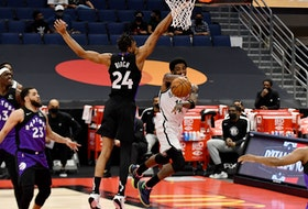 Brooklyn Nets guard Kyrie Irving passes the ball as Toronto Raptors centre Khem Birch defends on Thursday night.