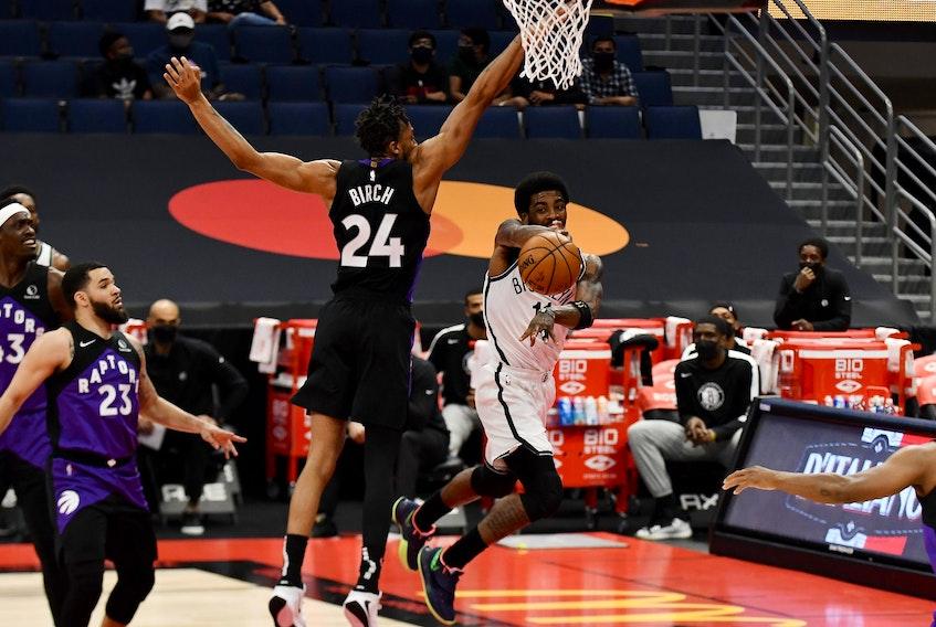 Brooklyn Nets guard Kyrie Irving passes the ball as Toronto Raptors centre Khem Birch defends on Thursday night.