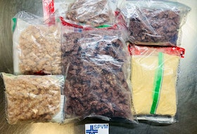 A photo supplied by Montreal police shows packages of fentanyl seized worth about $1.4 million, the largest such seizure in Quebec history. Curtis Harris, 37, Eddwich Simon, 34, and Jamall McKenzie, 40, face charges in connection with the seizure.