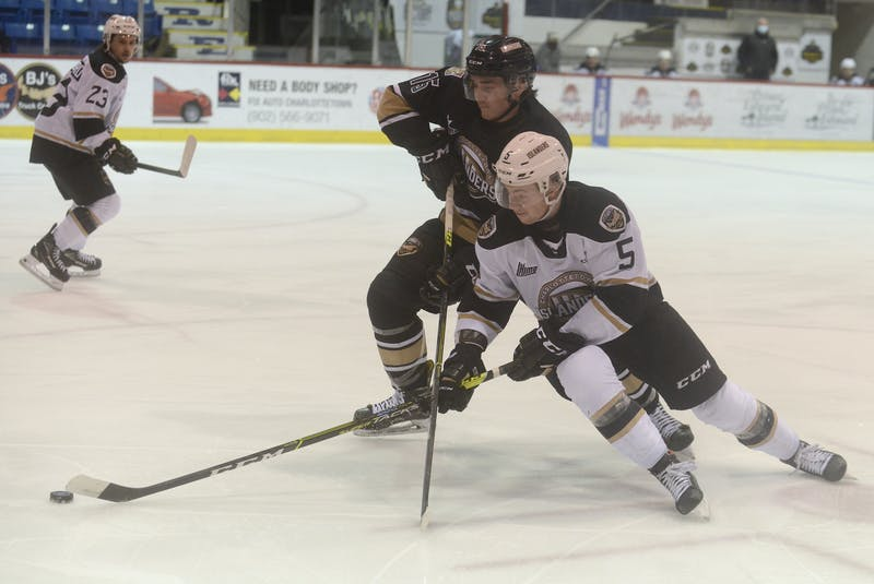 Charlottetown Islanders Team White defenceman Braeden Virtue, right, tries to get to the puck while Charlottetown Islanders Team Black forward Ben Boyd applies the pressure during Wednesday's intrasquad game at Eastlink Centre. - Jason Malloy
