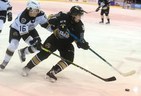 Charlottetown Islanders Team Black defenceman Lukas Cormier, right, spins away from Charlottetown Islanders Team White forward Pat Guay during Wednesday's intrasquad game at Eastlink Centre.